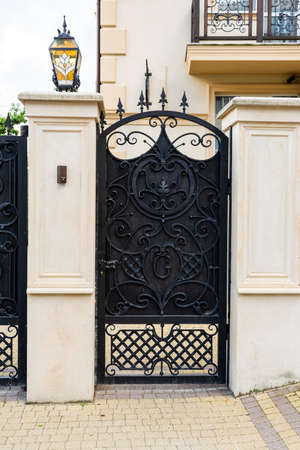 black forged metal gate with a fence at the entrance with a stone fence,  Standard-Bild