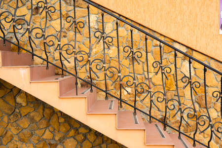 metal forged openwork railing on the steps in the tile