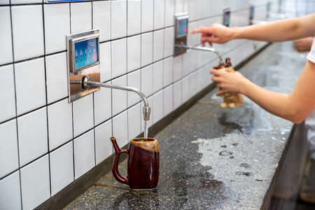 Water is poured into a special cup in the pump room of mineral waters, Imagens