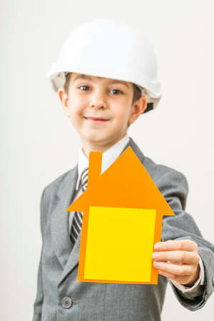 boy holding a cardboard house in hands on his head construction helmet, he himself is an architect