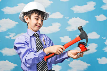 boy holding a cardboard house in hands on his head construction helmet Standard-Bild