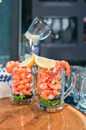 Fresh shrimps with lemon in a beer glass on a wooden tray Standard-Bild