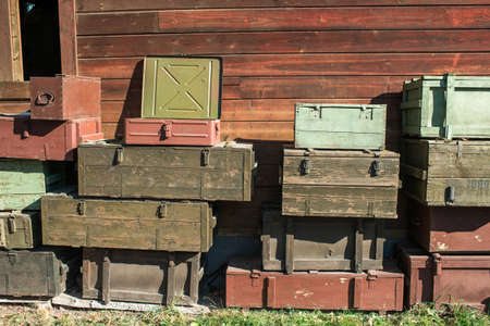 wooden boxes for storing weapons and transportation are standing outside under a wall