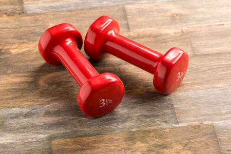 small red dumbbells for children and fitness lie on the floor Stock Photo