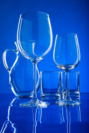 clean glassware for drinks on a blue background, glasses for wine and juice with a carafe