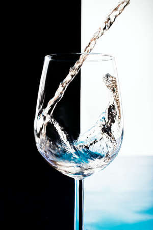 white wine is poured into a glass goblet