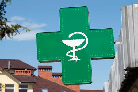 pharmacy sign, cross sign with medicine symbol of a snake above the thicket Stock fotó
