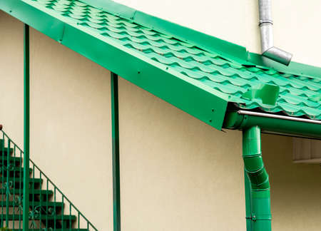 colored metal roof tiles with rain gutter 写真素材