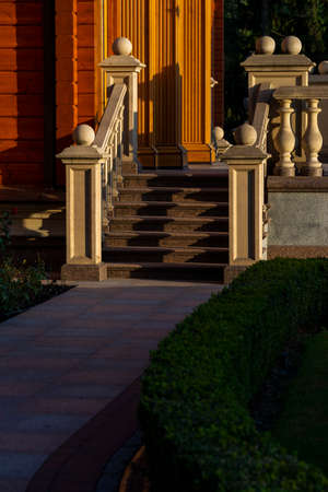 stone steps with balusters and stone balls in architecture, boxwood bushes coming from the steps