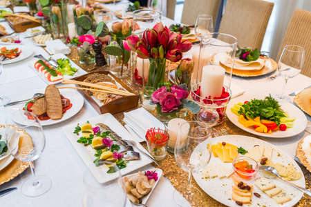 Served table with cold appetizers and decorated with flowers Standard-Bild