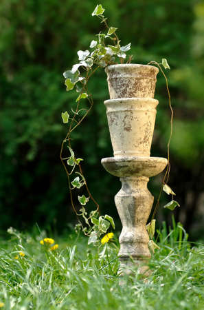 ceramic pot on a pedestal in the garden among the tall grass