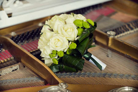bouquet of white roses for the bride on the piano strings