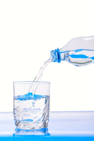 pouring raw clear water into a glass beaker