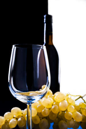 light grapes near a glass of wine on a contrasting background of black and belogovino glass