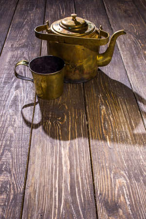 brass kettle with a bronze bowl on wooden table