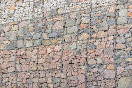 boulders constrained mesh creating a wall Stock Photo