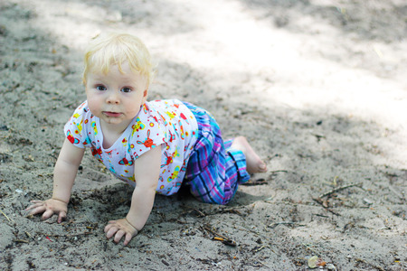 bebe gateando: Baby crawling and eating sand Foto de archivo
