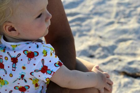 upbringing: A child in the arms of an adult looks at the sea