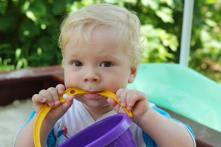 nibbles: A child in a sandbox nibbles bucket handle Stock Photo