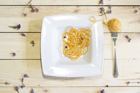 hank: Hank on a fork like spaghetti in the plate on a wooden background
