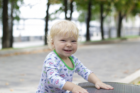 A small child learns to walk near the benches, toddler Stock Photo