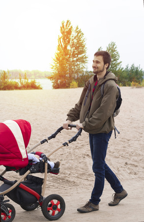 Young father helps mother, he walks with a baby carriage in the park by the river Stock Photo