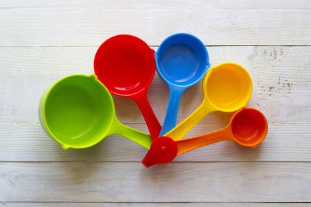 Colorful measuring spoons for kitchen on a white wooden background Stock Photo