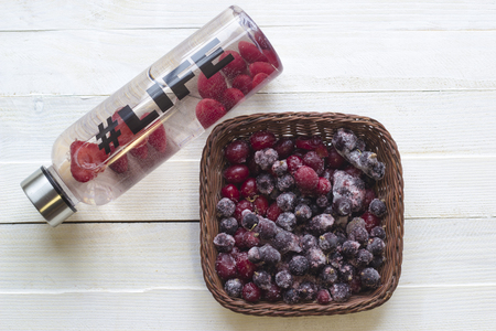 thin ice: Bottle with refreshing drink, water with strawberry slices, with hashtag #life and basket with frozen berries on white wooden background