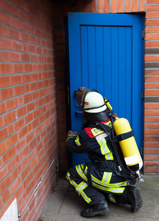 reachability: Firefighter in mission and opening a door Stock Photo