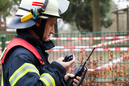 radio communication: Fire Fighter in action with radio set Stock Photo