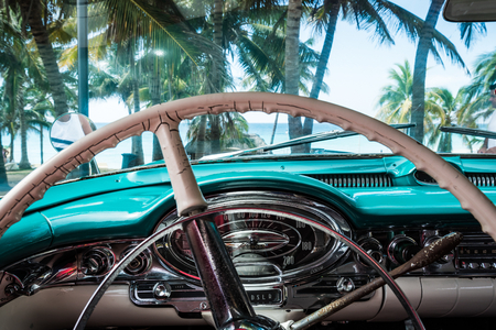 cuba: Cockpit view from a vintage car in Cuba with view of Palms Stock Photo