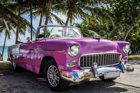 Pink cabriolet classic car parked on the beach in Cuba