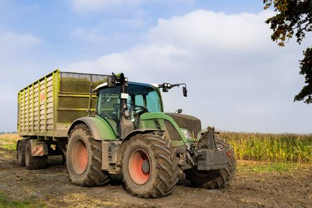 agricultural application tractor: Tractor with trailer full from corn Stock Photo