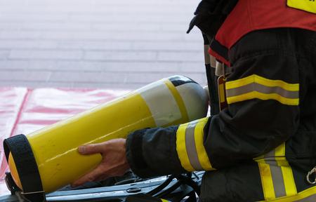 bombero: Cilindro de ox�geno en uso con un bombero