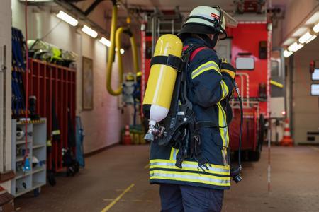 bombera: Bombero con cilindros de oxígeno en el cuerpo de bomberos