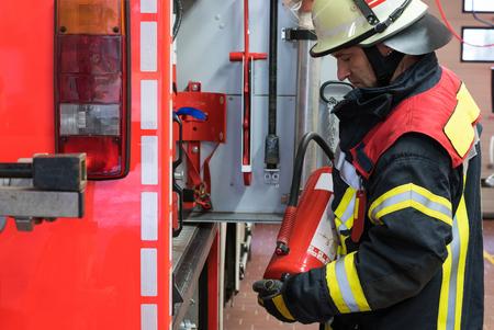 bombero: Bombero con extintor en el cami�n de bomberos