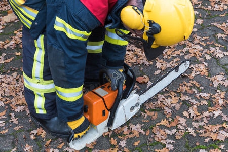 chainsaw: Fireman in action with chainsaw Stock Photo