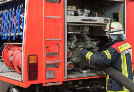 emergency vehicle: Firefighter uses a water hose to the Emergency Vehicle