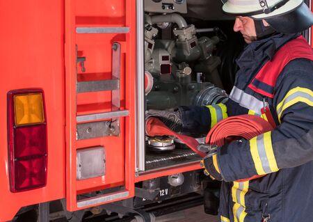 bombera: Firfighter con manguera de bomberos en el camión de bomberos