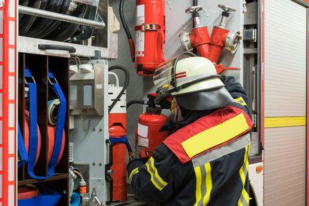 bombera: Firfighter con extintor en el camión de bomberos