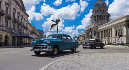 capitolio: American blue and black vintage car on the crossroad in Havana Cuba with Capitolio view in the background Editorial