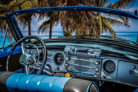 HDR - Interior view from a american blue cabriolet vintage car on the beach