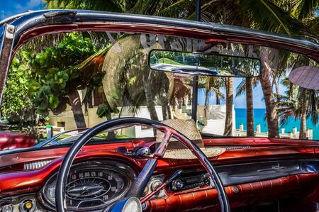 HDR - Interior view from a american red cabriolet vintage car on the beach