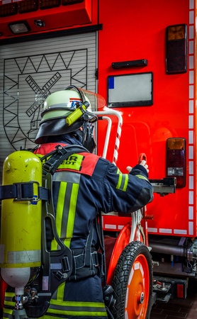 luft: Firefighter in action on the emergency vehicle with oxygen bottle and respiratory protection mask - HDR