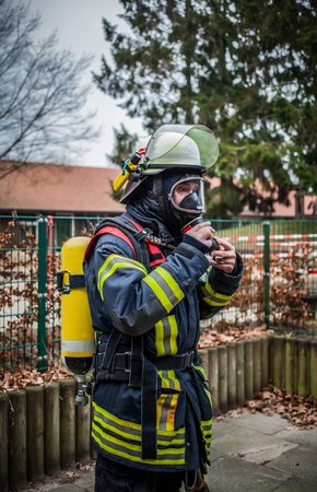 Firefighter outdoor in action with oxygen bottle and respiratory protection mask - HDR