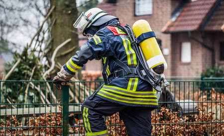reachability: Firefighter outdoor in action and climbing with oxygen bottle and mask - HDR