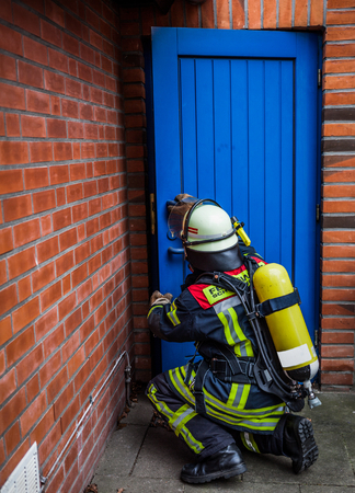 reachability: HDR - Firefighter opens a door in action with oxygen bottle and respiratory protection mask