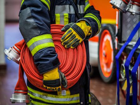 HDR - Brandweerman in actie met een rolde brandslang op het noodvoertuig Stockfoto