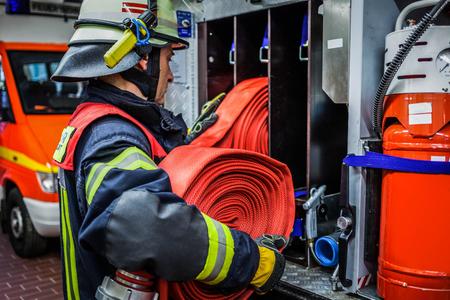 HDR - Brandweerman in actie met een opgerolde brandslang op het hulpvoertuig
