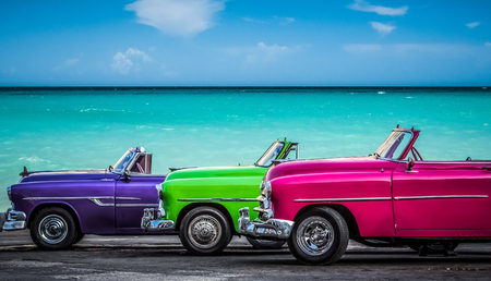 Havana, Cuba - July 05, 2015: HDR - Three colorfully Chevrolet Cabriolet classic cars parked before the Caribbean Sea on the Malecon in Havana Cuba  - Serie Cuba Reportage